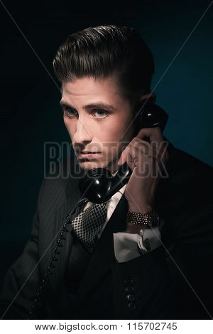 Classic Vintage Businessman In Suit And Tie On The Phone. Hair Combed Back. Against Dark Blue Wall.