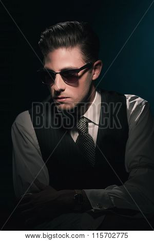 Classic Stylish Fashion Man With Sunglasses In Waistcoat And Tie. Greasy Hair Combed Back. Against D