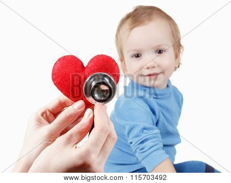 Child and cardiologist, heart symbol in hand, stethoscope.