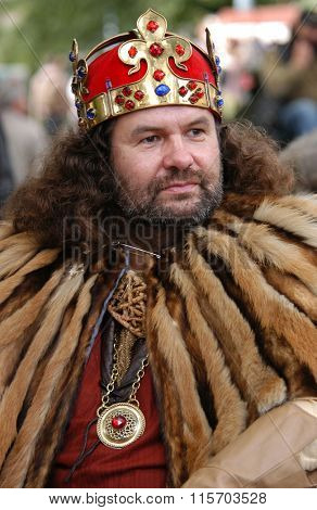 PRAGUE, CZECH REPUBLIC - SEPTEMBER 24, 2004: Bearded man dressed as King Charles IV of Bohemia wearing the Wenceslas Crown attends the wine festival Vinohradske Vinobrani in Prague, Czech Republic.