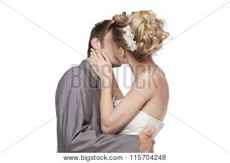 Studio portrait of young elegant enamoured just married bride and groom embracing and kissing on white  background