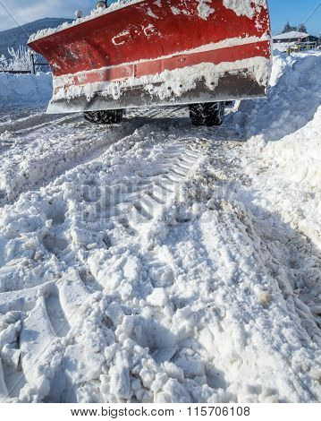 Closeup Of Snowy Road And Snow Plow Truck