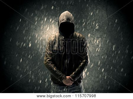 A faceless misterious man in hoodie and leather jacket standing in the dark with a visible silhouette concept