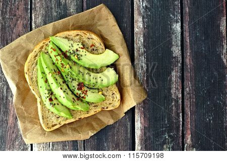Open avocado sandwich on paper against rustic wood