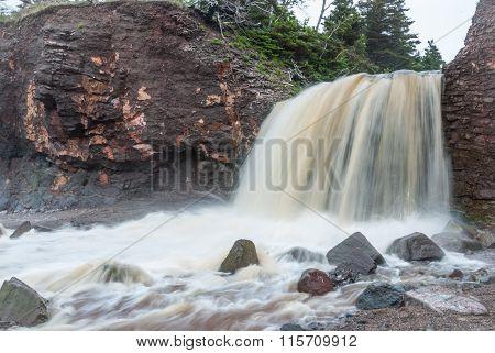 Springtime Nova Scotia coastline in June. Waterfalls from a cliff onto rocky pebble beach.