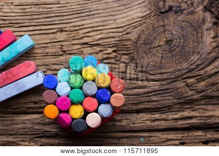 Pastel crayons and pigment dust on old wooden background.