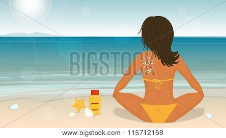 Young girl sunbathes on a beach and caring about her skin