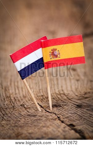 Flags of Netherlands and Spain on wooden background