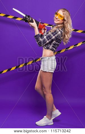 Brunette With An Electric Jigsaw On A Blue Background With The Protective Tape In The Yellow Buildin