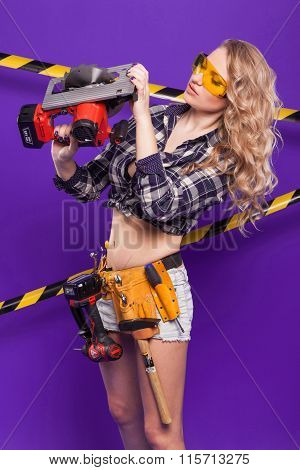 Blonde With Big Breasts In Yellow Building Protective Glasses On Purple Background With The Protecti