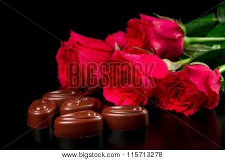 Chocolate candies with a bouquet of roses on a black background