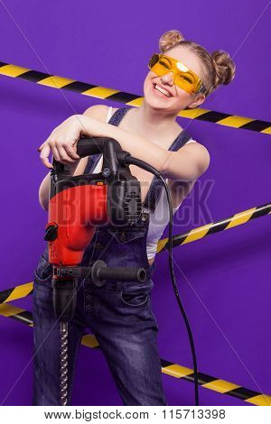 Sexy Blonde In Denim Overalls And Protective Glasses Is Building On A Blue Background With The Prote
