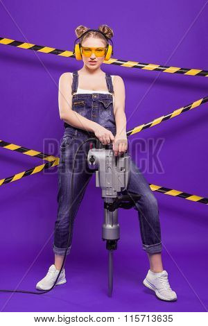 Blonde In A Suit, Sunglasses And Protective Construction Headphones With A Jackhammer On A Purple Ba