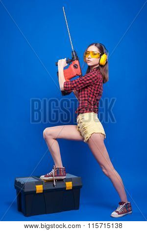 Girl On A Blue Background With A Hammer Drill And A Box Of Tools In Building Protective Headphones A