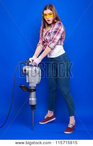 Sexy Brunette In A Yellow Building With Glasses And A Plaid Shirt On A Blue Background Holding A Lar