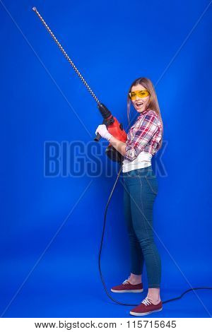 Sexy Brunette In Building Protective Headphones And Sunglasses Holding A Hammer Drill