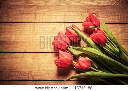 Fresh red tulip flowers bouquet on wood. Natural spring or Valentine's Day, Mother's Day theme.