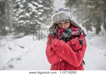 Woman winter hiking. Beautiful young woman enjoying the falling snow dressed in a winter scarf and cap and with a satchel on her back with copyspace.