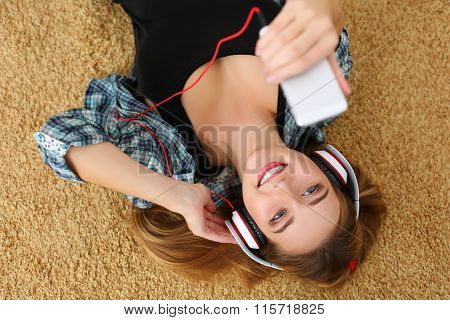 Beautiful Blonde Smiling Woman Lying On Carpet Floor Wearing Headphones, Holding Cell Phone And List