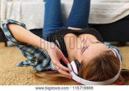 Beautiful Blonde Smiling Woman Lying On Carpet Floor Wearing Headphones