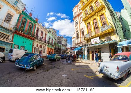 HAVANA,CUBA- JANUARY 19,2015 : Street scene with old classic cars and colorful buildings in Havana
