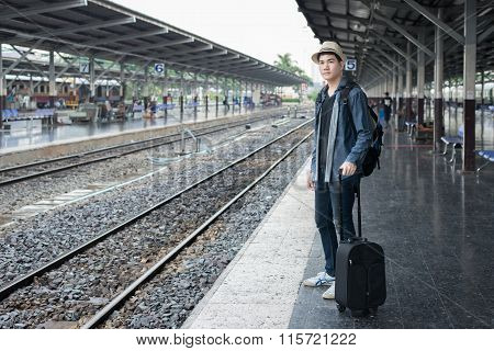 Asian Young Man Waiting Train For Journey At Station