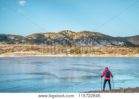 male hiker at a shore of frozen Horsetooth Reservoir near Fort Collins, Colorado  with Athurs's Rock in background