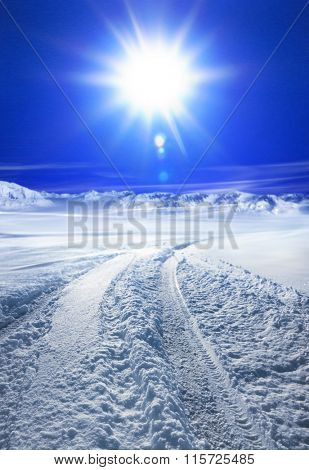 Snow covered road in winter with mountains in the distance