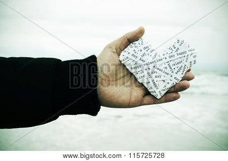 closeup of the hand of a young man holding a heart made-up with paper strips with the text happy valentines day, with a vignette added