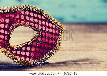 an elegant red and golden carnival mask on a rustic wooden surface