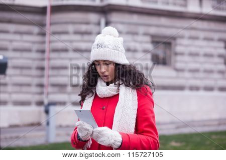 Woman In Red Coat With Smartphone In Hands Going Through The City And Looking Shop Windows. Urban Sc