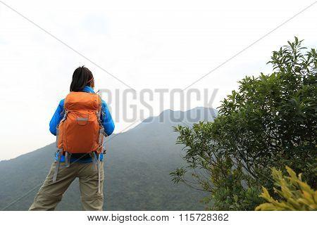 young woman backpacker hiking on mountan peak