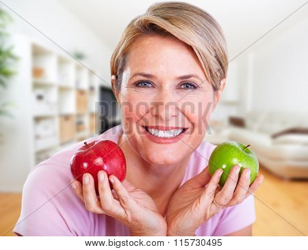 Mature smiling woman with apple.