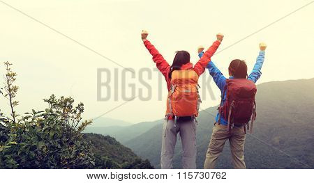 two successful backpackers hiking on mountain peak