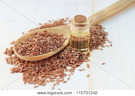 Flax seeds in wooden spoon and oil