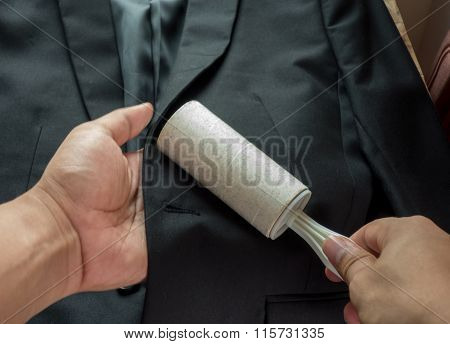 Dry Cleaning And Business Theme: A Man Hand With Black Suit Holding A White Sticky Brush For Cleanin