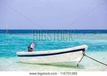 Small white fishing boat rests on the sea