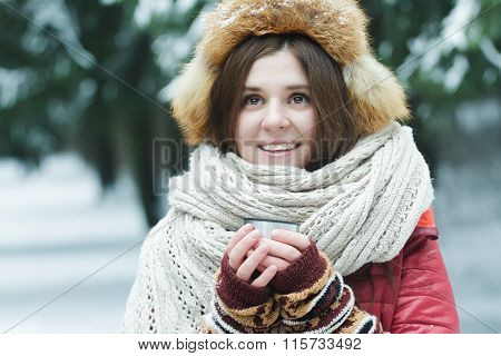 Outdoor winter portrait of cheerful young lady holding tourist vacuum flask cup with hot drink