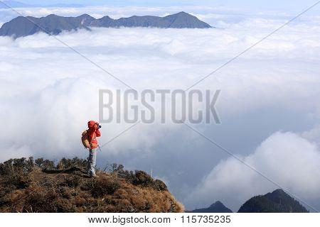 one young woman backpacker hiking on mountainpeak