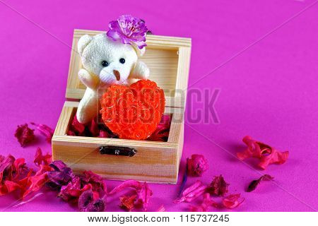 Small teddy bear holding Love in wooden box
