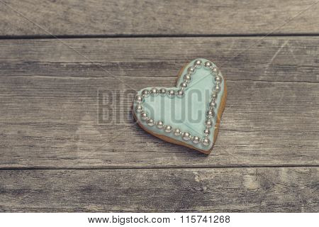 Heart Cookie Covered With Blue Icing And Edible Pearl Beads