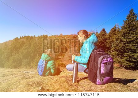 mother and son travel in mountains drinking hot tea