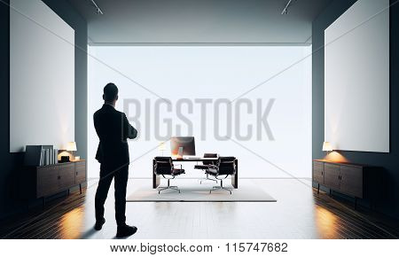 Businessman stands in modern office with two empty canvas. Color