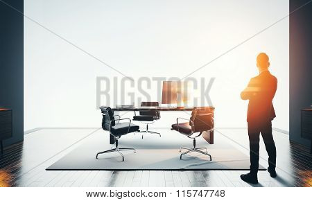 Businessman stands in modern office and looking at horizon. Bokeh effects