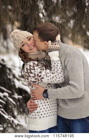 Cheerful, happy, enamored, smiling girl, woman and man, boy, guy in winter, snow, cold forest, true love in frozen, winter, forest, kiss in cheek, couple, affectionate, attentive, caring, relationship, intimate, lovers