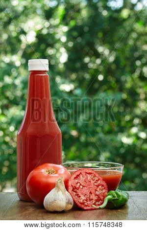 Tomato, garlic, hot pepper, bottle of ketchup and juice