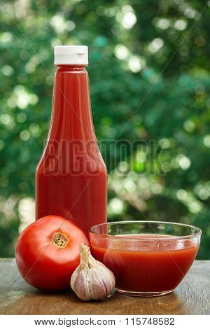 Tomato, garlic, glass bowl and bottle of ketchup