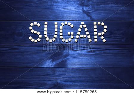 The Word 'sugar', Built From White Cubes Pieces Of Sugar On Background  Of Panel From Vintag