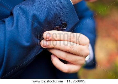 dressing. Closeup of a man in jacket correcting sleeves.