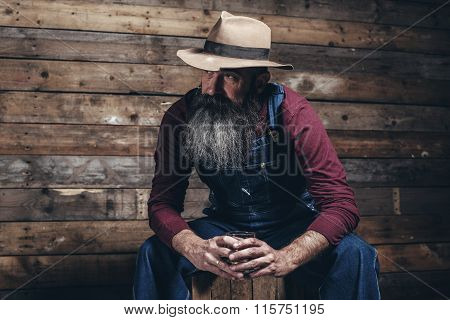 Vintage Worker Man With Long Gray Beard In Jeans Dungarees Holding Whiskey. Sitting On Wooden Crate